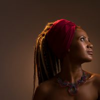 Profile view of beautiful african woman with dreadlocks, wearing red headscarf and looking away.